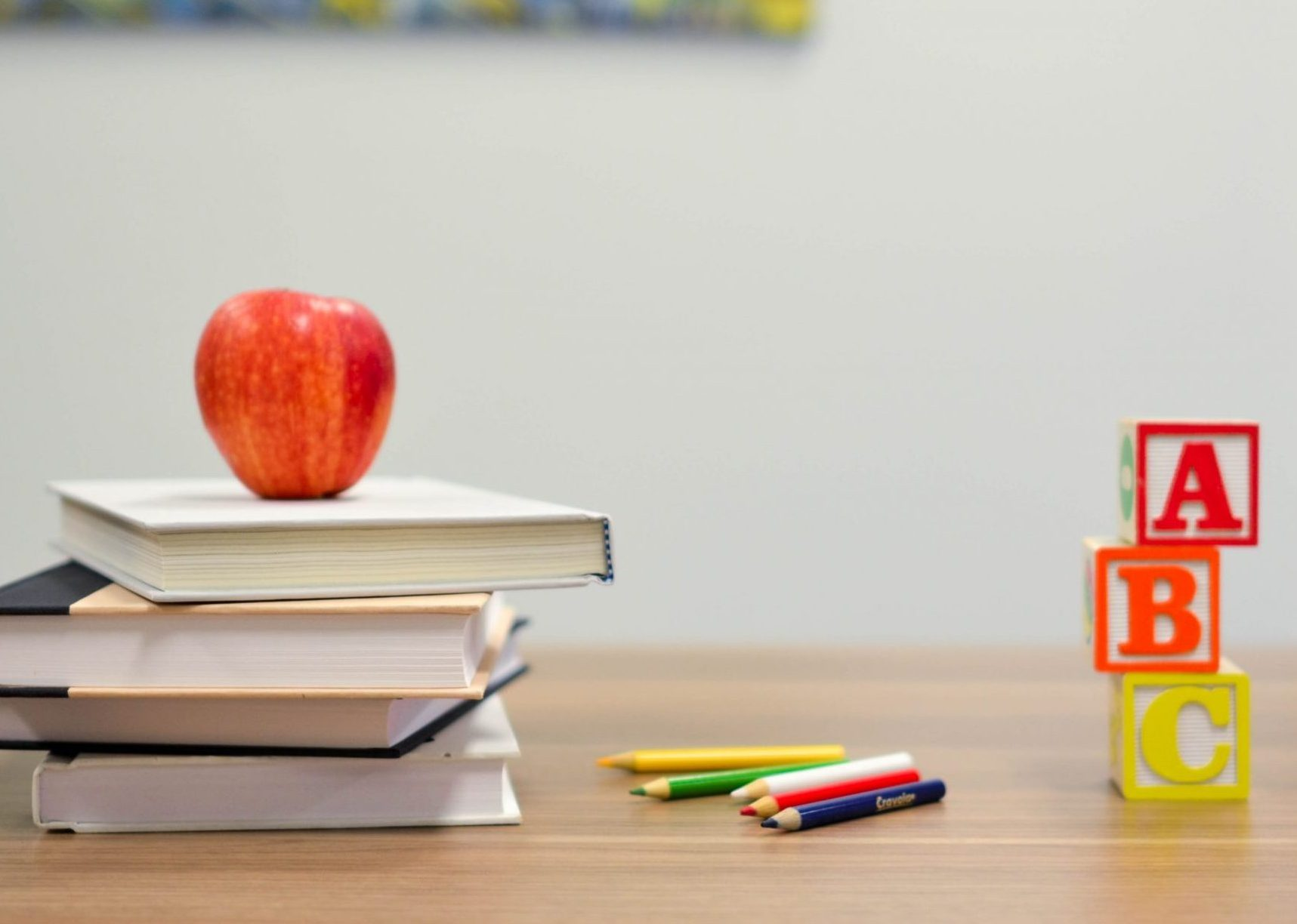 Desk with apple on books, colored pencils, and blocks