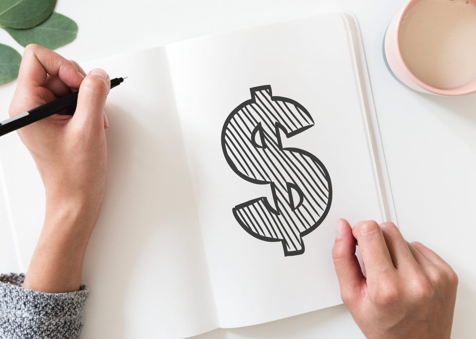 Big dollar sign written in book with woman's hands