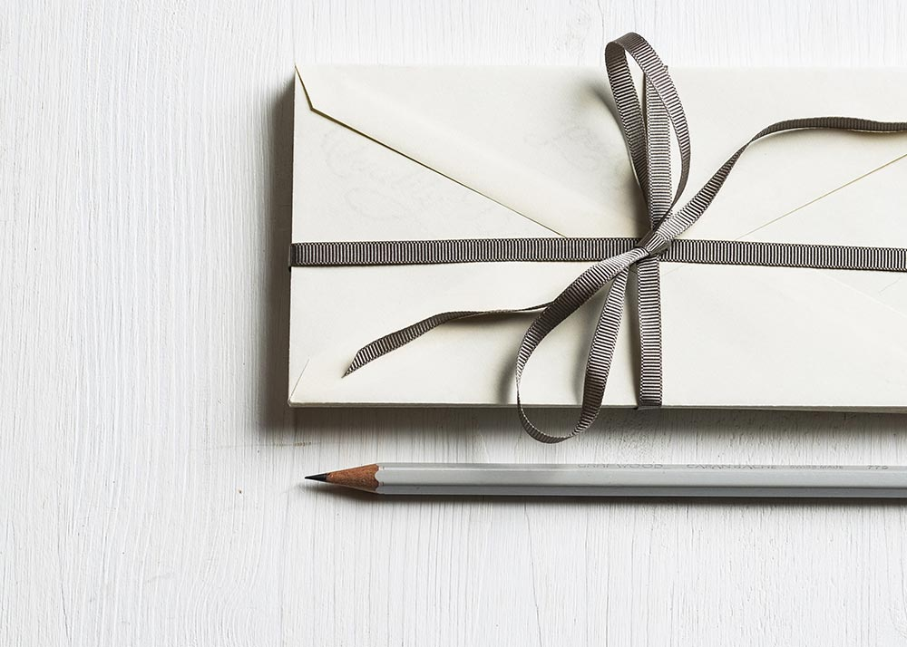 Pencil and stack of envelopes wrapped with a ribbon