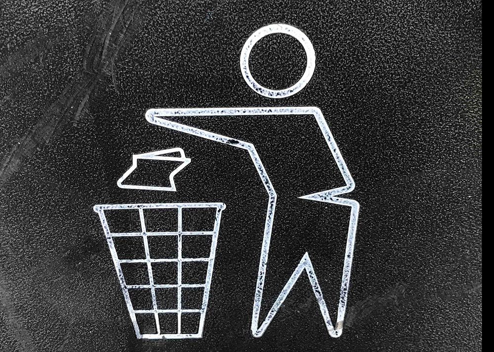 Line drawing of person tossing trash in a basket
