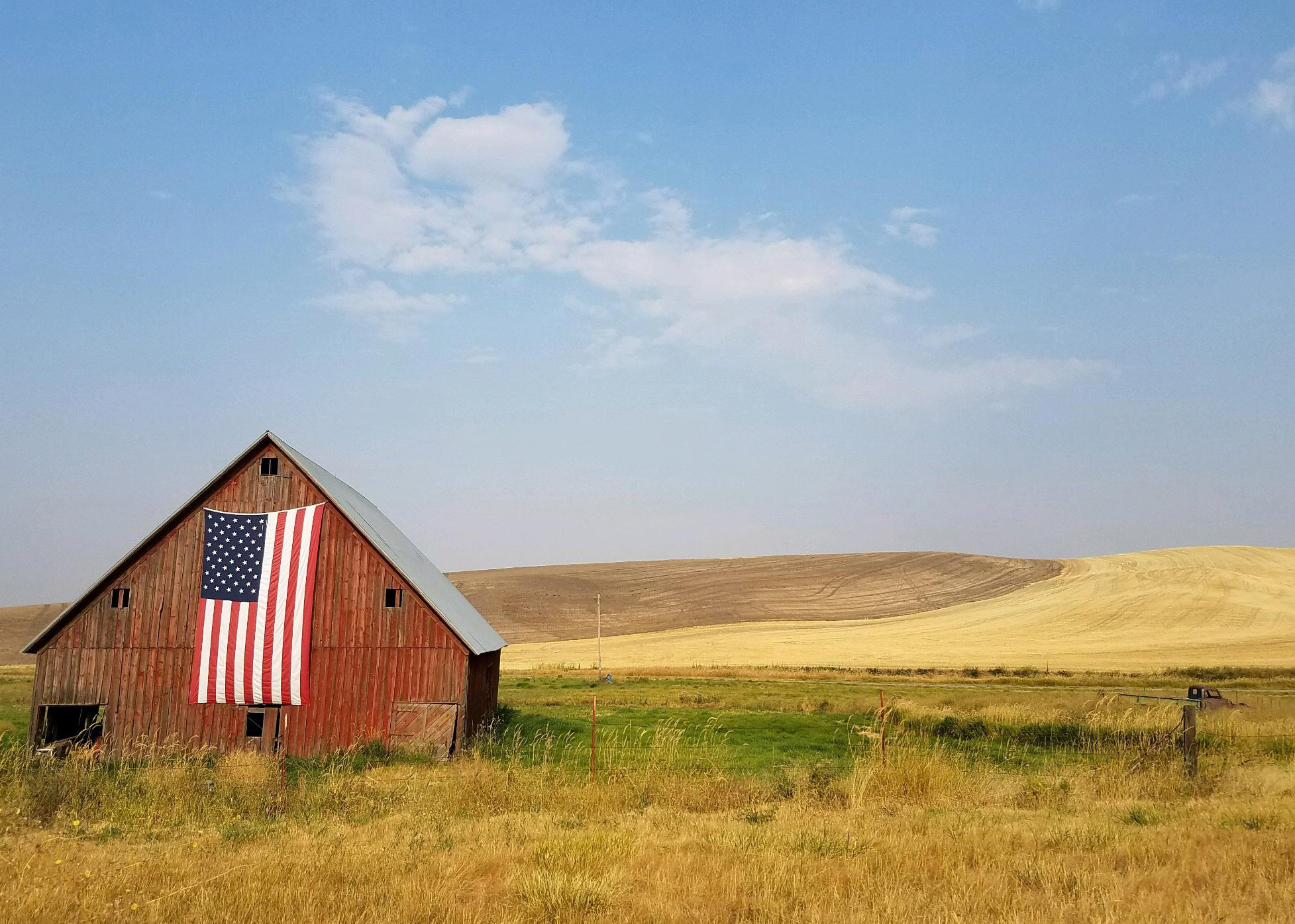 Old red barn with American flag hanging on the front in the countryside