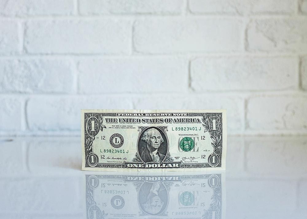 One dollar bill standing on table