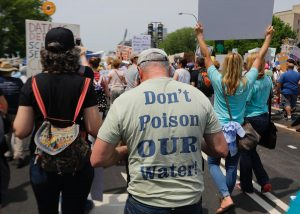 "Back of a protestor's shirt that says, ""Don't Poison Our Water!"""