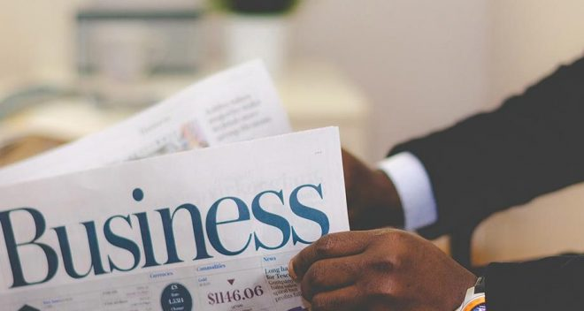 A man reading the business section of a newspaper